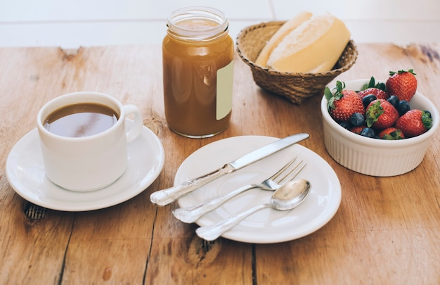 Coffee cup; set of cutlery; jam mason jar; bread and berries on wooden table