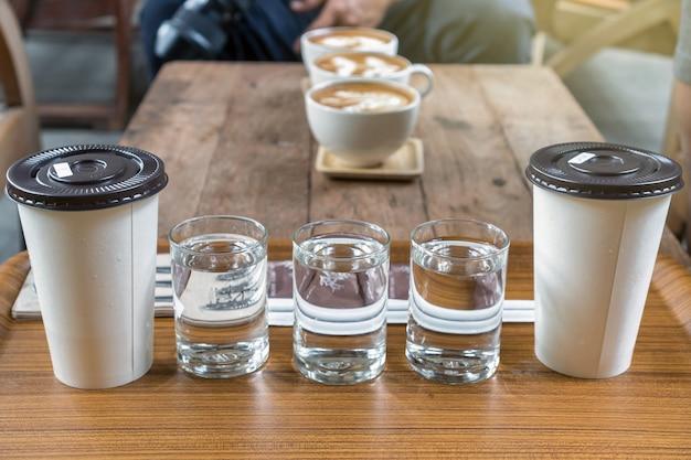 흐리게 사진 위에 종이 컵에 물과 아이스 커피의 유리로 구성된 커피 컵 세트