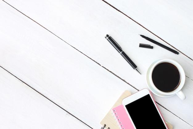 Кофейная чашка смартфон и ручка, ноутбук на белом деревянный стол.