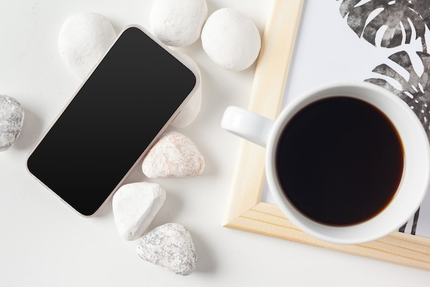Coffee cup and smartphone, top view