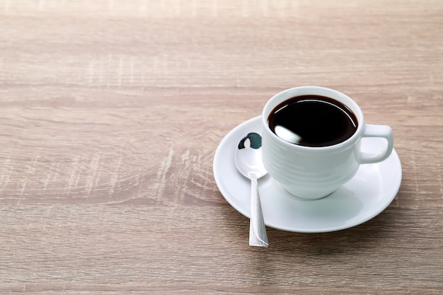 Coffee cup and spoon on wooden table
