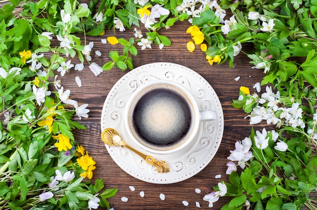 Coffee cup and spring flowers on rustic wooden background