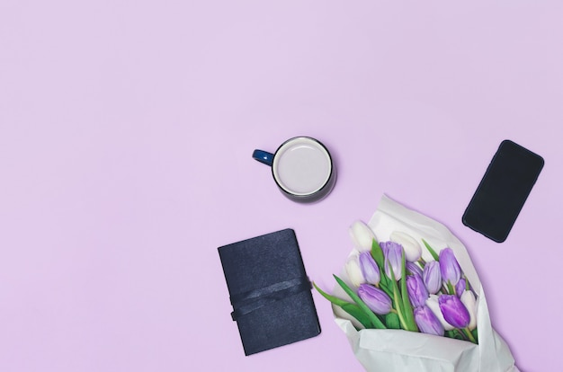 Чашка кофе, весенний тюльпан цветы и на столе. вид сверху.