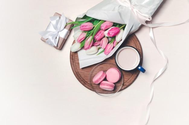 Кофейная чашка, цветки тюльпана весны и розовые macarons на деревянном столе. вид сверху.