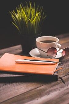コーヒーカップ文房具メモ帳作業木製テーブルフラワー鉢植え