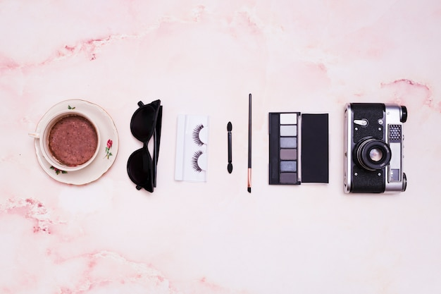 Coffee cup; sunglasses; eyelashes; makeup brush; eyeshadow palette and vintage camera on pink textured backdrop