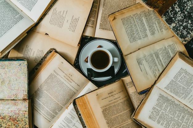 Чашка кофе в окружении открытых старинных книг
