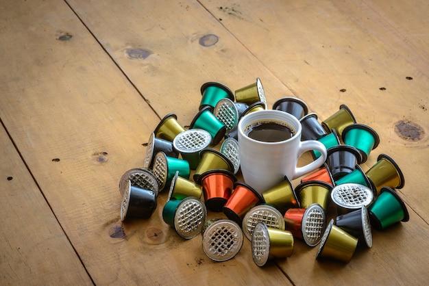 나무 테이블에 사용된 커피 캡슐로 둘러싸인 커피 컵 프리미엄 사진