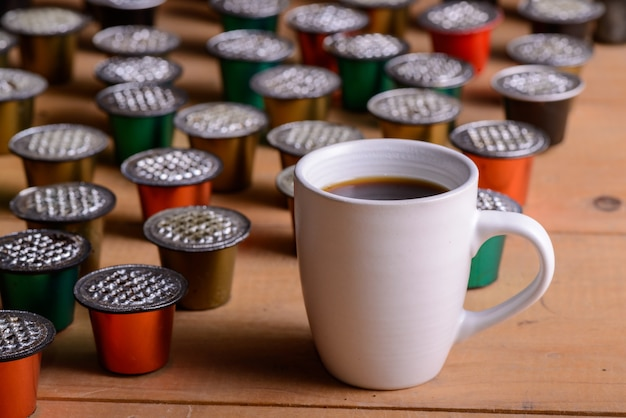 나무 테이블에 사용된 커피 캡슐로 둘러싸인 커피 컵
