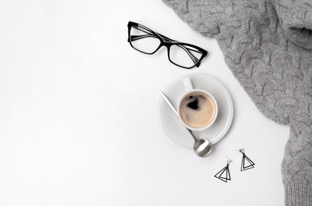 Кофейная чашка, свитер, помады и стаканы. женская или осенняя концепция
