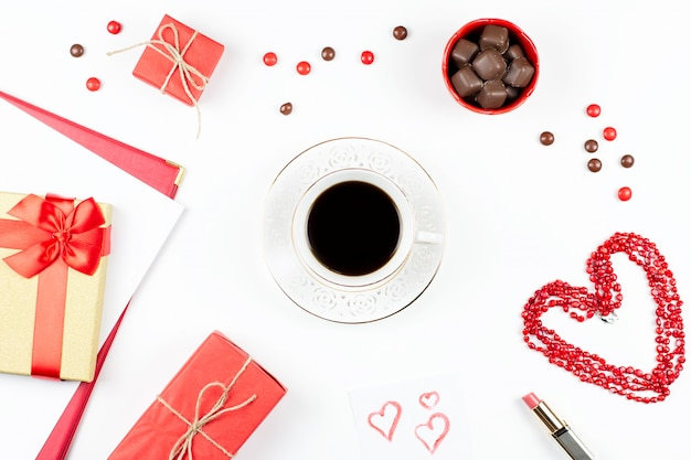 Coffee cup, sweets, lipstick, heart shape and gift box on white surface