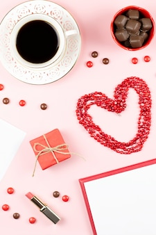 Coffee cup, sweets, lipstick, heart shape and giftbox on pink background. women's day concept flat lay.
