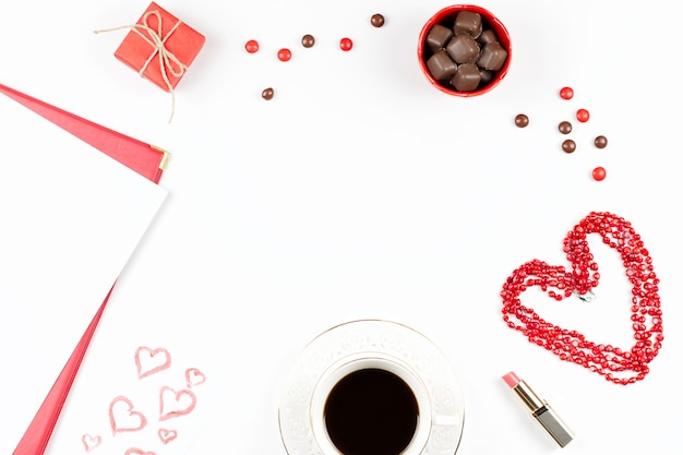 Coffee cup, sweets, lipstick, heart shape and giftbox on white background. valentine's day concept frame.