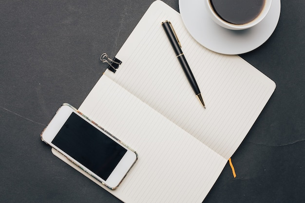 Coffee cup on the table notepad with a pen phone technology