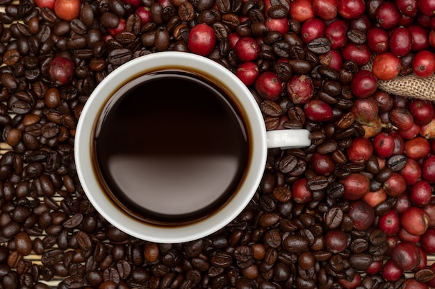 Coffee cup on table with cherries and coffee beans