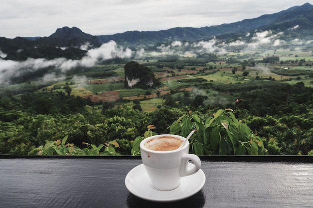 Coffee cup on table with mountain views in the morning as a background