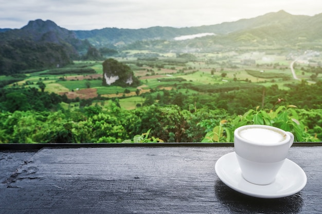Coffee cup on table with mountain views in the morning