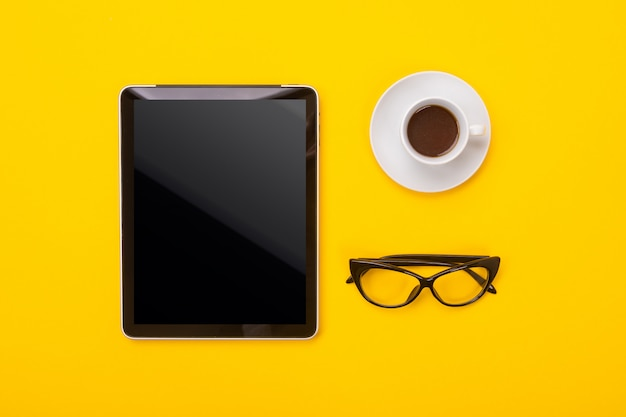 Coffee cup, tablet and glasses isolated on yellow background