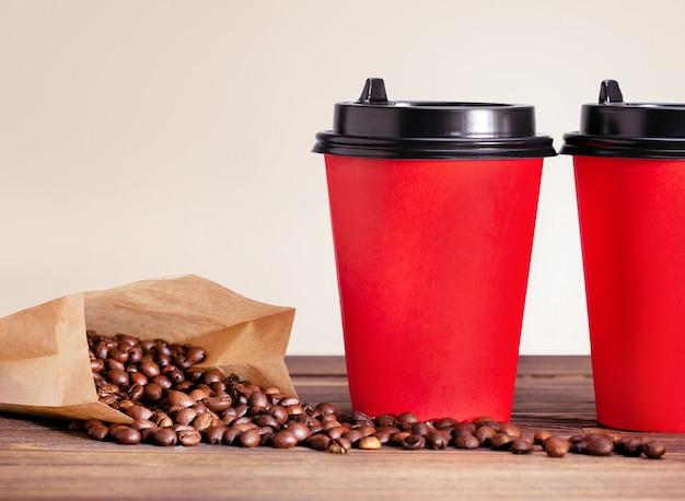 Кофейная чашка, чтобы пойти и мешок с фасолью на деревянный стол