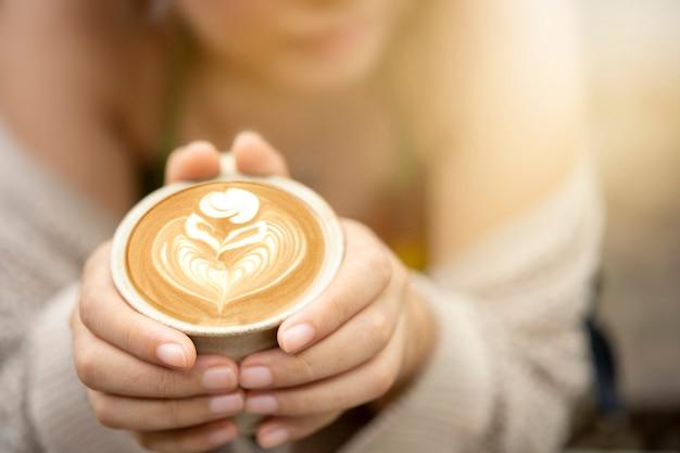 Вид сверху кофейной чашки рук женщины. кофе латте искусство в утренней концепции.