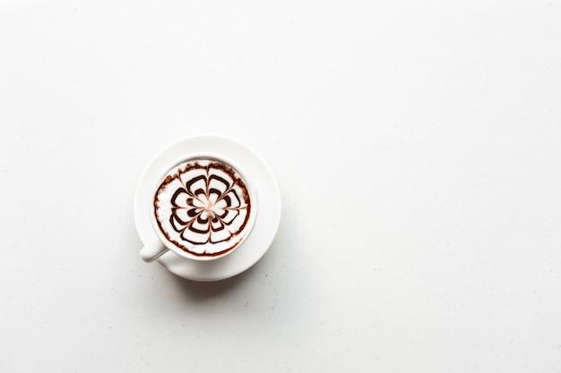 白いテーブルの上のコーヒーカップの上面図。コピースペース