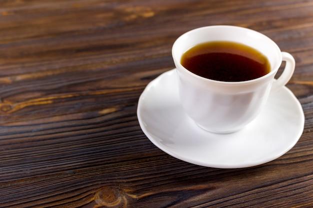 Вид сверху кофейной чашки на фоне деревянного стола.