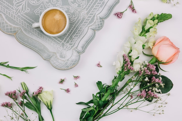 Coffee cup on tray with limonium; rose; eustoma and snapdragons flower on white background