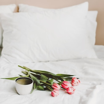 Coffee cup and tulips in bed on white sheets