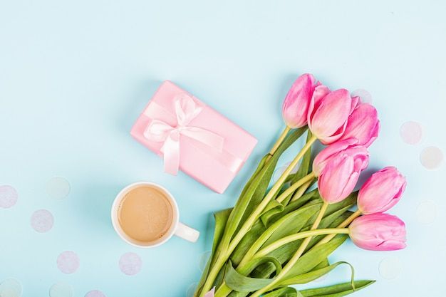 Coffee cup, tulips and gift box on blue
