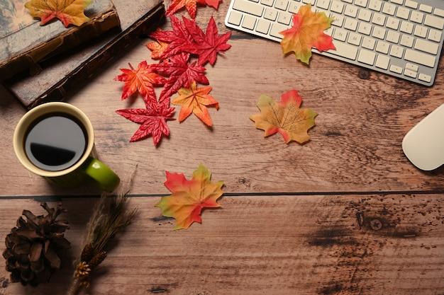 커피 컵, 빈티지 책, 안경, 가을 단풍나무 잎이 나무 테이블에 있습니다.