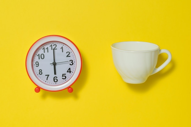 Coffee cup and white analog alarm clock on yellow background. the concept of lifting the tone in the morning. flat lay.