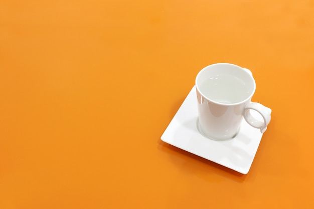 Coffee cup white on top table orange, water mug white on background orange