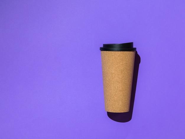 보라색 표면에 검은 색 뚜껑이있는 커피 컵