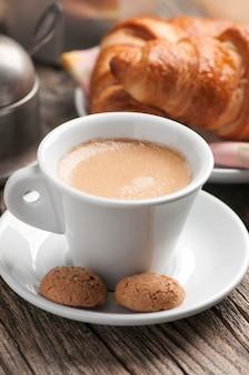나무 테이블에 크루아상 아침 식사와 함께 커피 컵