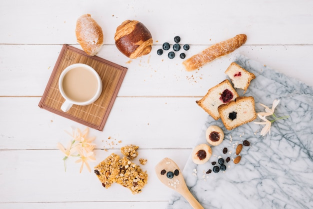Coffee cup with bakery on wooden table