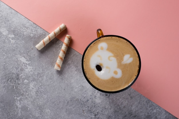 Coffee cup with bear latte art on marble and color table