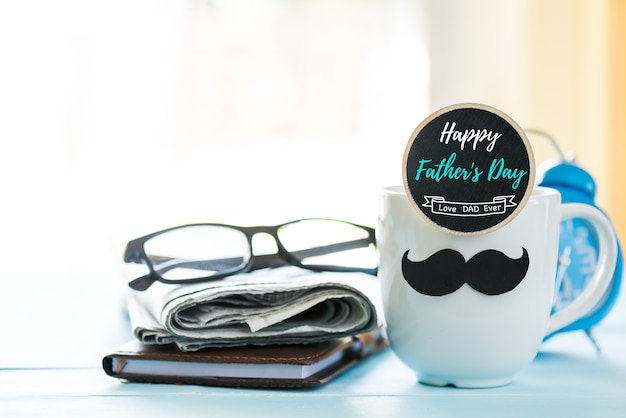 Coffee cup with black paper mustache, newspaper on wooden table background.
