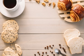 Coffee cup with buns and cookies on wooden table