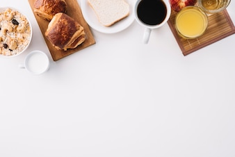 Coffee cup with buns and oatmeal on table