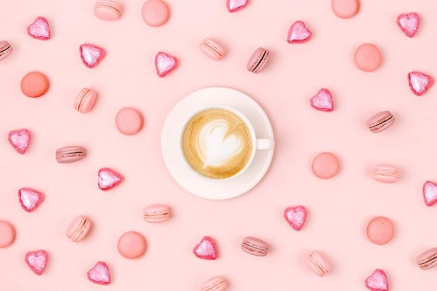 淡いピンクの背景にキャンディーとマカロンのコーヒーカップ。フラットレイ、上面図