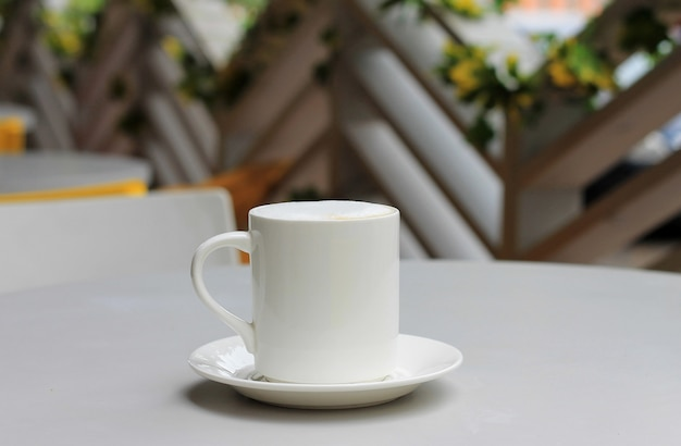 Coffee cup with cappuccino on a table in a cafe