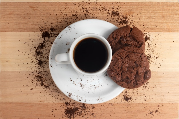 Coffee cup with chocolate cookies on the table.