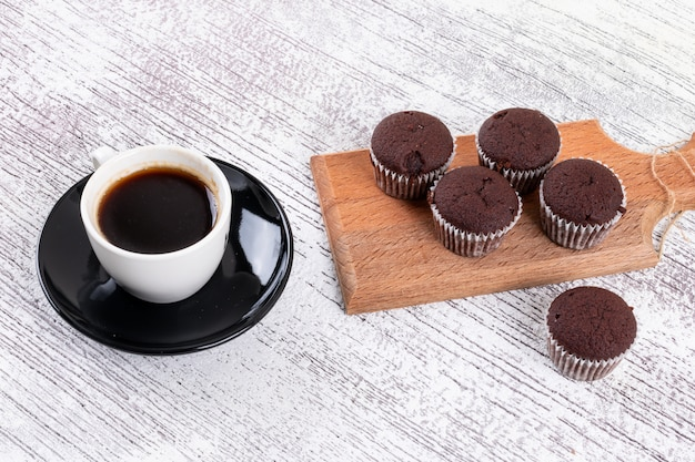 Coffee cup with chocolate muffins on wooden board