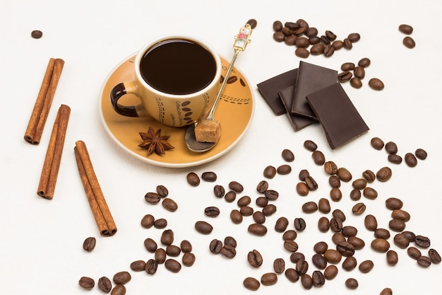 Coffee cup, with cinnamon sticks, chocolate and coffee grains around on white background