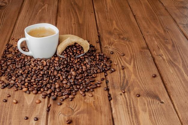 木製テーブルの上のコーヒーバッグとコーヒーカップ。上からの眺め