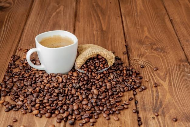 木製のテーブルの上のコーヒーバッグとコーヒーカップ。上から見る。