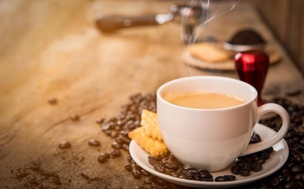 나무 테이블에 커피 콩을 넣은 커피 컵