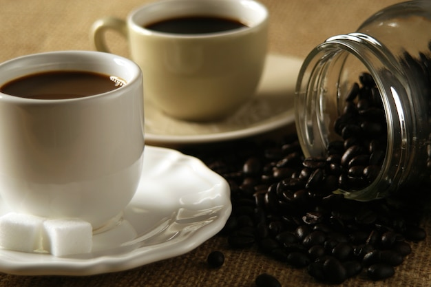 Coffee in the cup with coffee beans around.