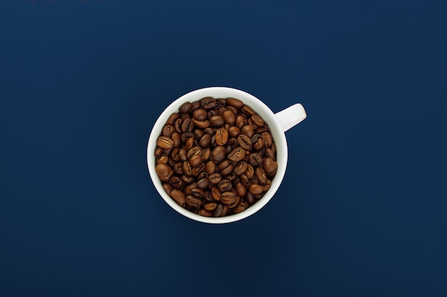 Coffee cup with coffee beans on blue background.