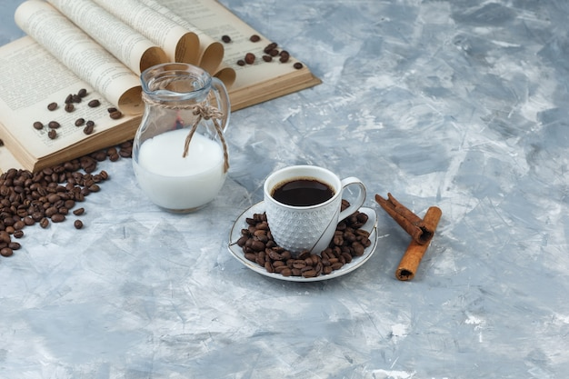 Coffee in a cup with coffee beans, book, cinnamon sticks, milk high angle view on a grey plaster background